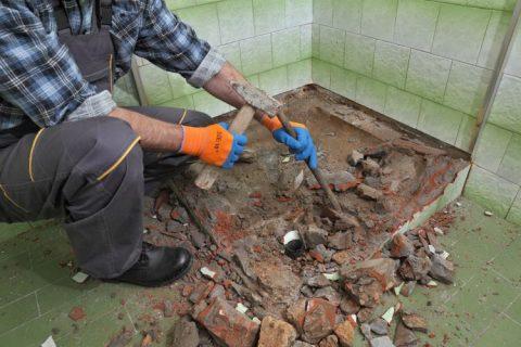 Image of hand demolition of shower recess in progress