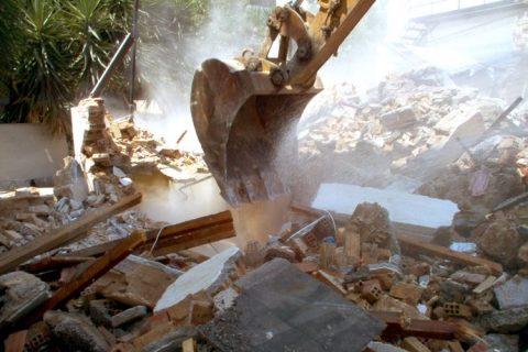 Image of excavator demolishing bricks and rubble